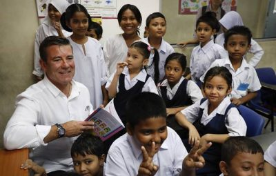 FILE - In this Jan. 26, 2017, file photo, New Zealand Immigration Minister Michael Woodhouse, left, smiles as he interacts with refugee students during his visit to the UNHCR Tzu Chi Education Centre in Selayang, outskirts of Kuala Lumpur, Malaysia. New Zealand announced Wednesday, April 19, 2017, that it is introducing tougher requirements for skilled overseas workers as it tries to control immigration numbers that have reached an all-time high. (AP Photo/Vincent Thian, File)