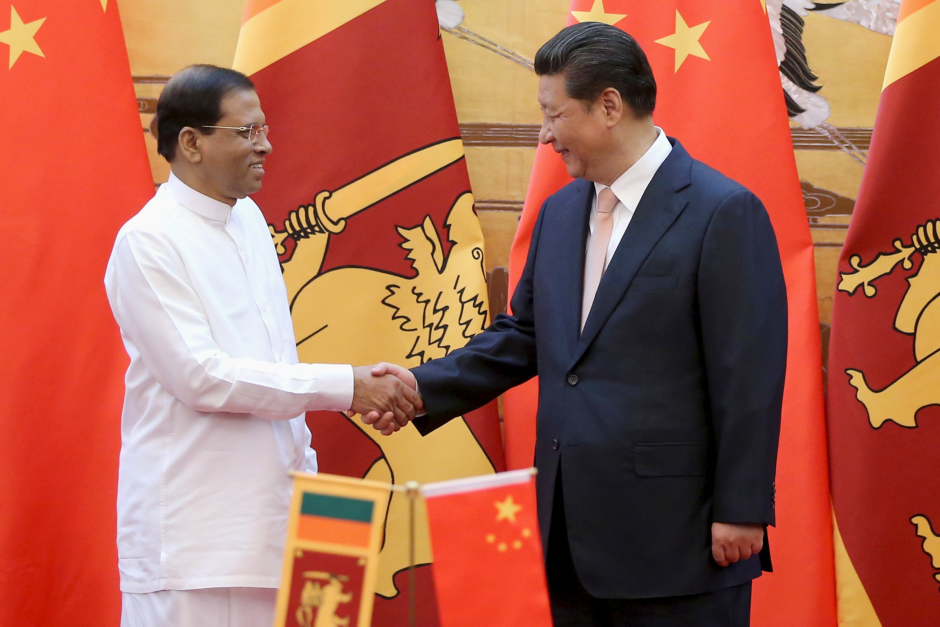Sri Lankan President Maithripala Sirisena (Left) shakes hands with Chinese President Xi Jinping (Right) during a signing ceremony in the Great Hall of the People on March 26, 2015 in Beijing, China. REUTERS/Feng Li-Poo/Pool - RTR4UWHZ